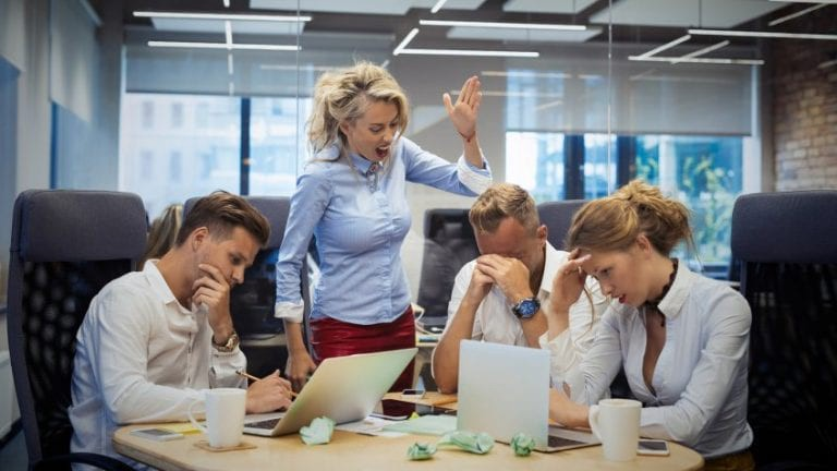 Angry woman boss berating her employees in a meeting