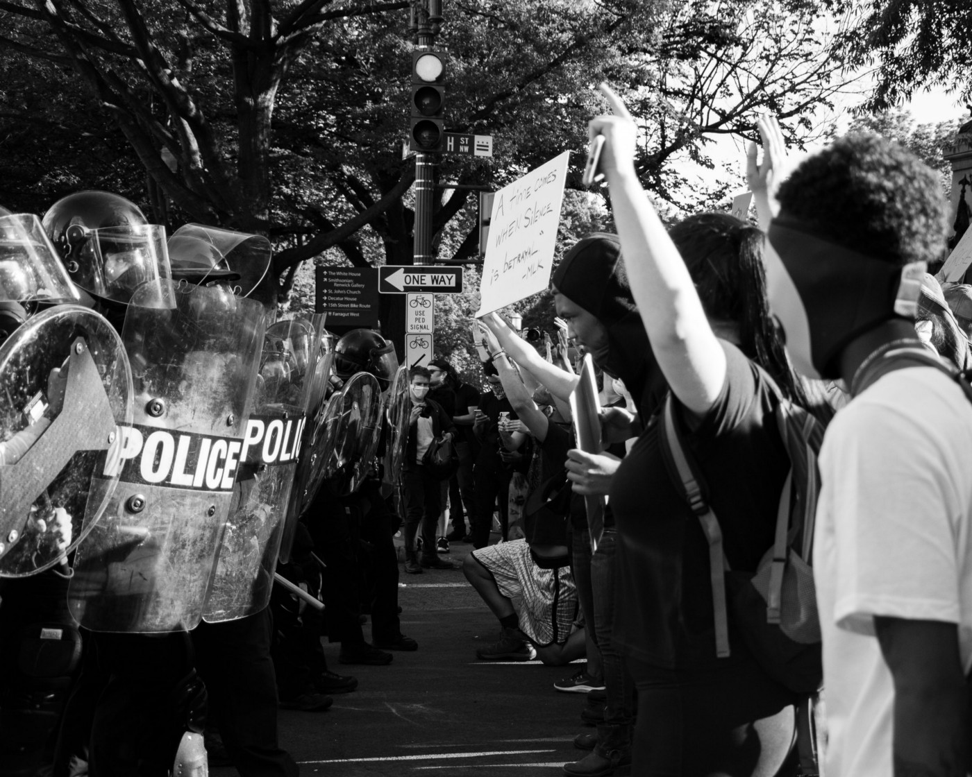 A photo of a Black Lives Matter protest showing a row of police on the left and a row of protested on the right