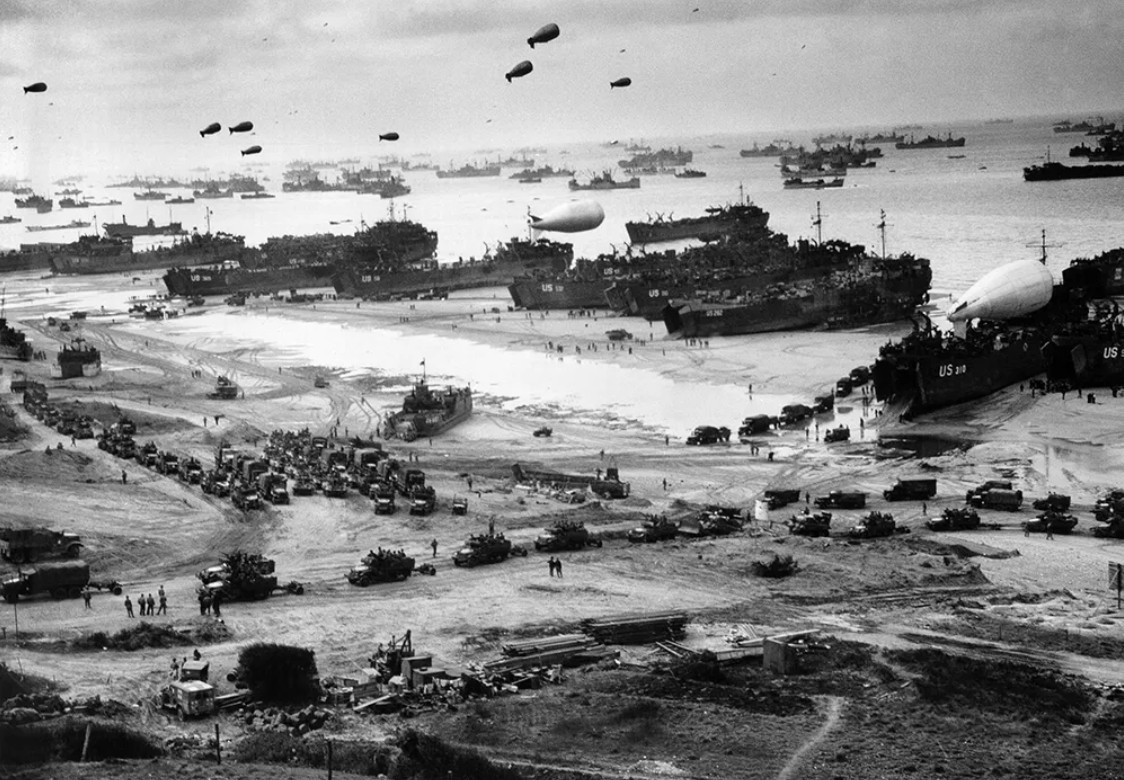 [Bird's-eye view of landing craft, barrage balloons, and allied troops landing in Normandy, France on D-Day]