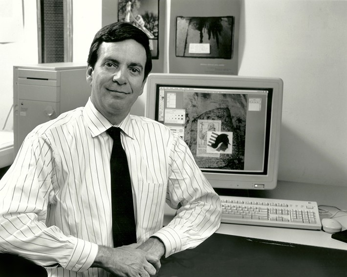 Philip B. Meggs, wearing a white striped dress shirt and dark necktie, sits in front of a computer at a desk. He's smiling and looking directly at the camera. He has short dark hair parted on his left side. His hands are clasped in front of his body. The computer screen has a montage of images related to graphic design history, such as the Rosetta Stone and petroglyphs. This is a black and white photo.