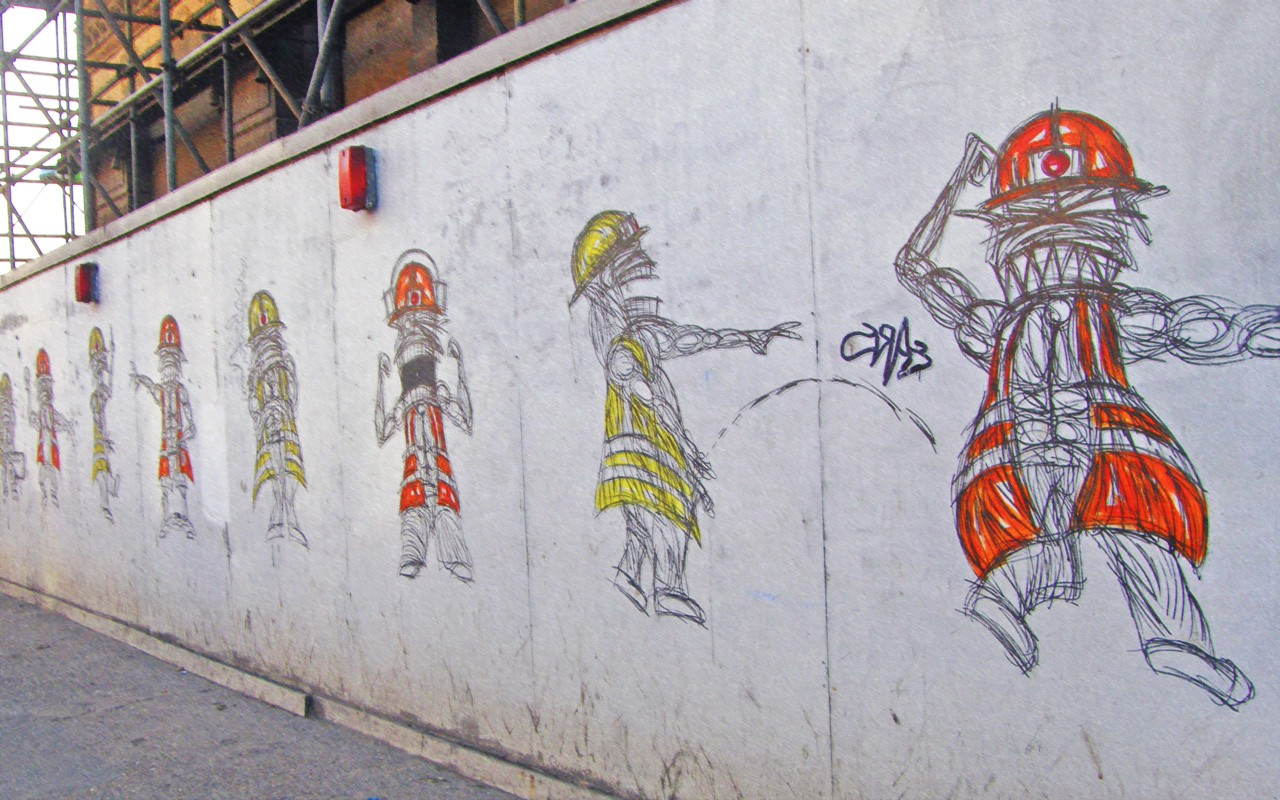 A mural of construction workers on boards blocking off construction work