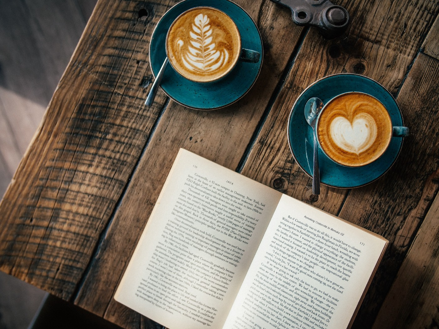 Two cups of coffee and an open book (at an angle).
