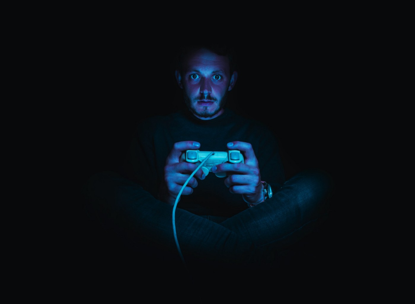 A frightened-looking man plays horror games in the dark.
