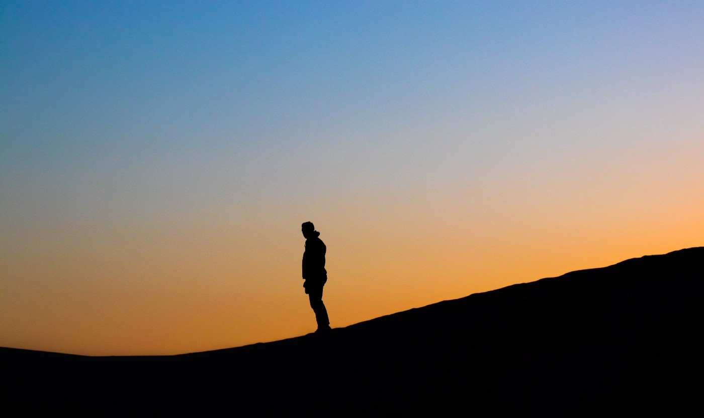 person standing alone in an open space, silhouetted against the sky