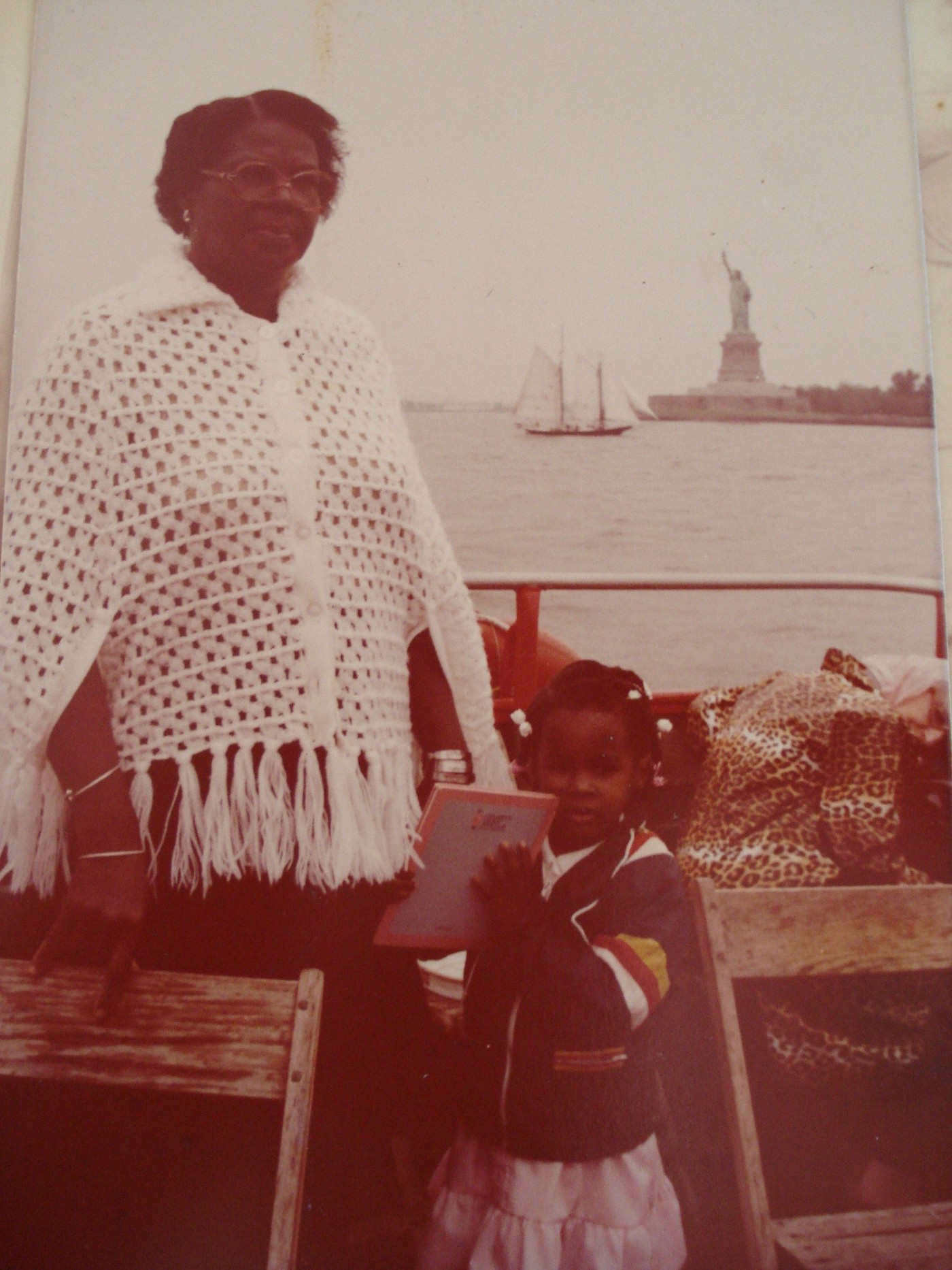 A Black woman and her grandchild stand together on a ferry with the Statue of Liberty in the distance. Circa 1983.
