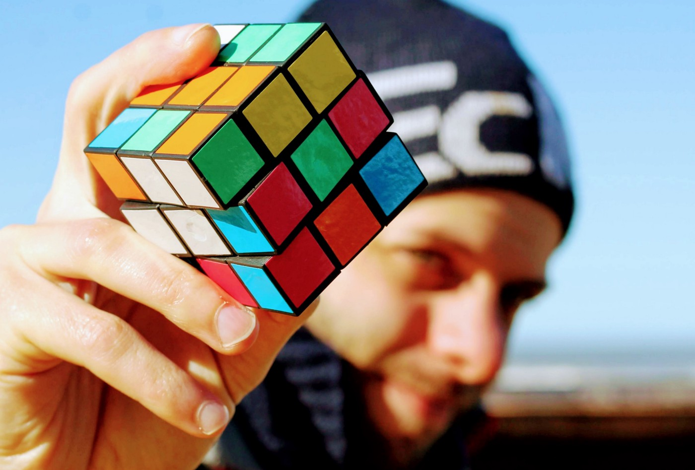 A man holding an unsolved rubik's cube