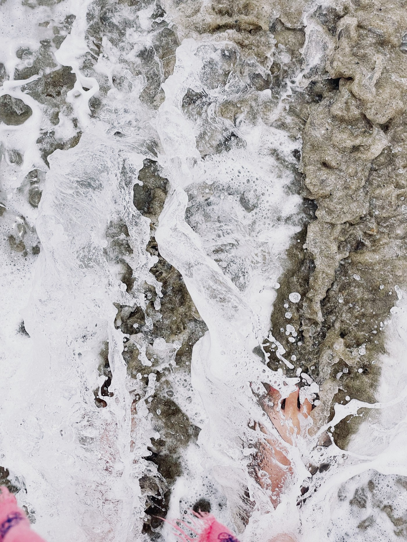Ocean waves and beach sand crashing and foaming at the feet of a woman