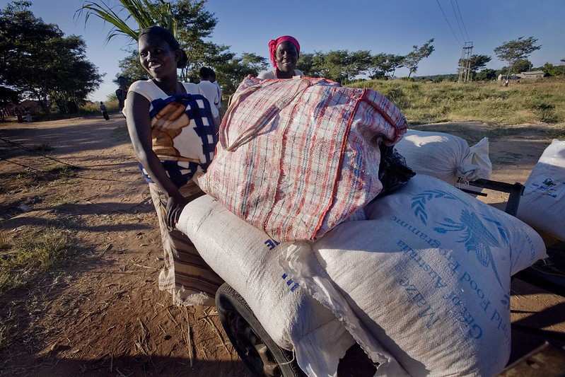 Two smiling Zimbabwean women push carts of donated food on a dirt road.