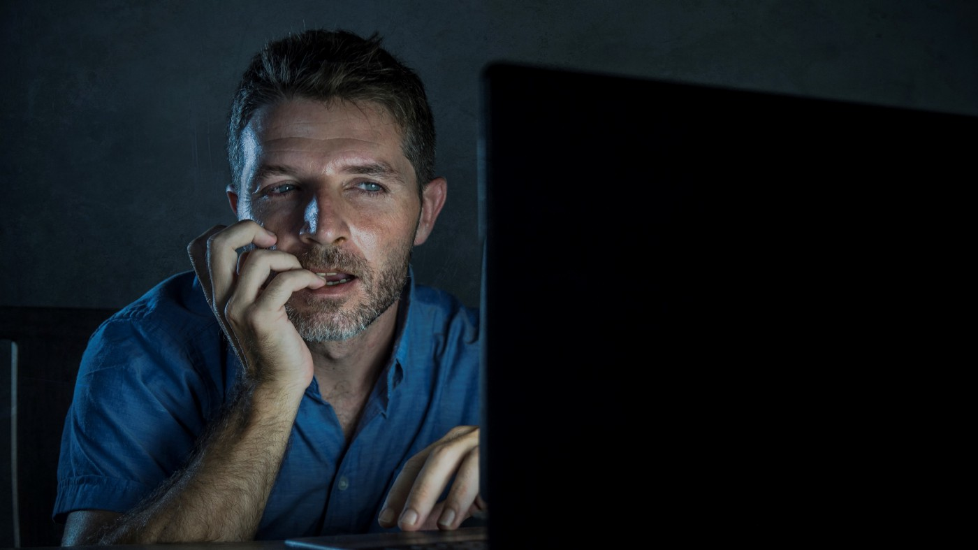 Young man who looks sexually aroused sitting in the dark watching his computer screen