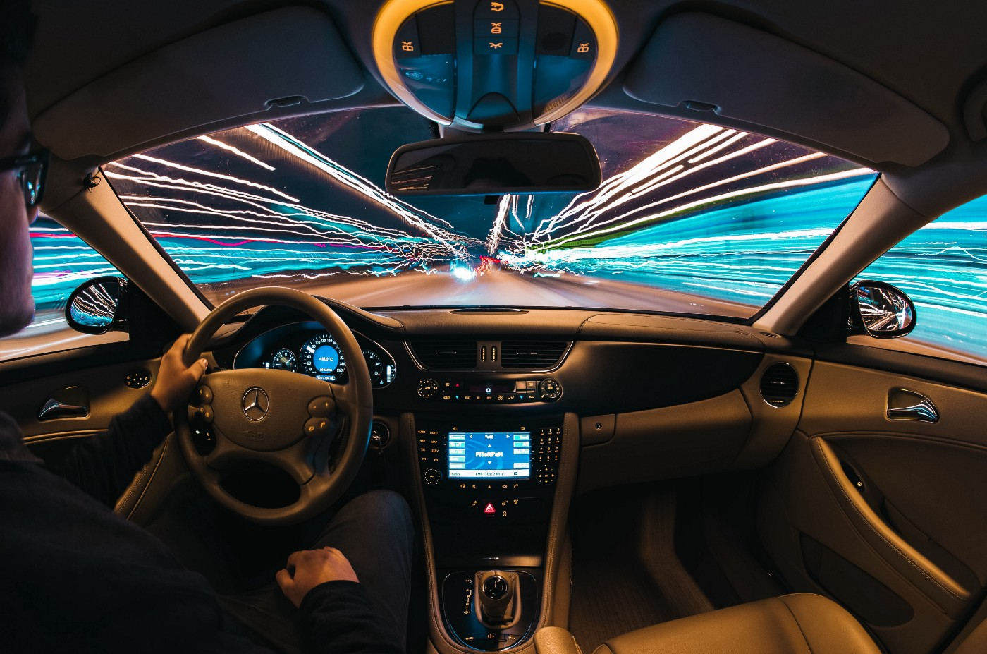 time lapse photo of a man driving a car taken from the interior, with visible lines of light outside the vehicle
