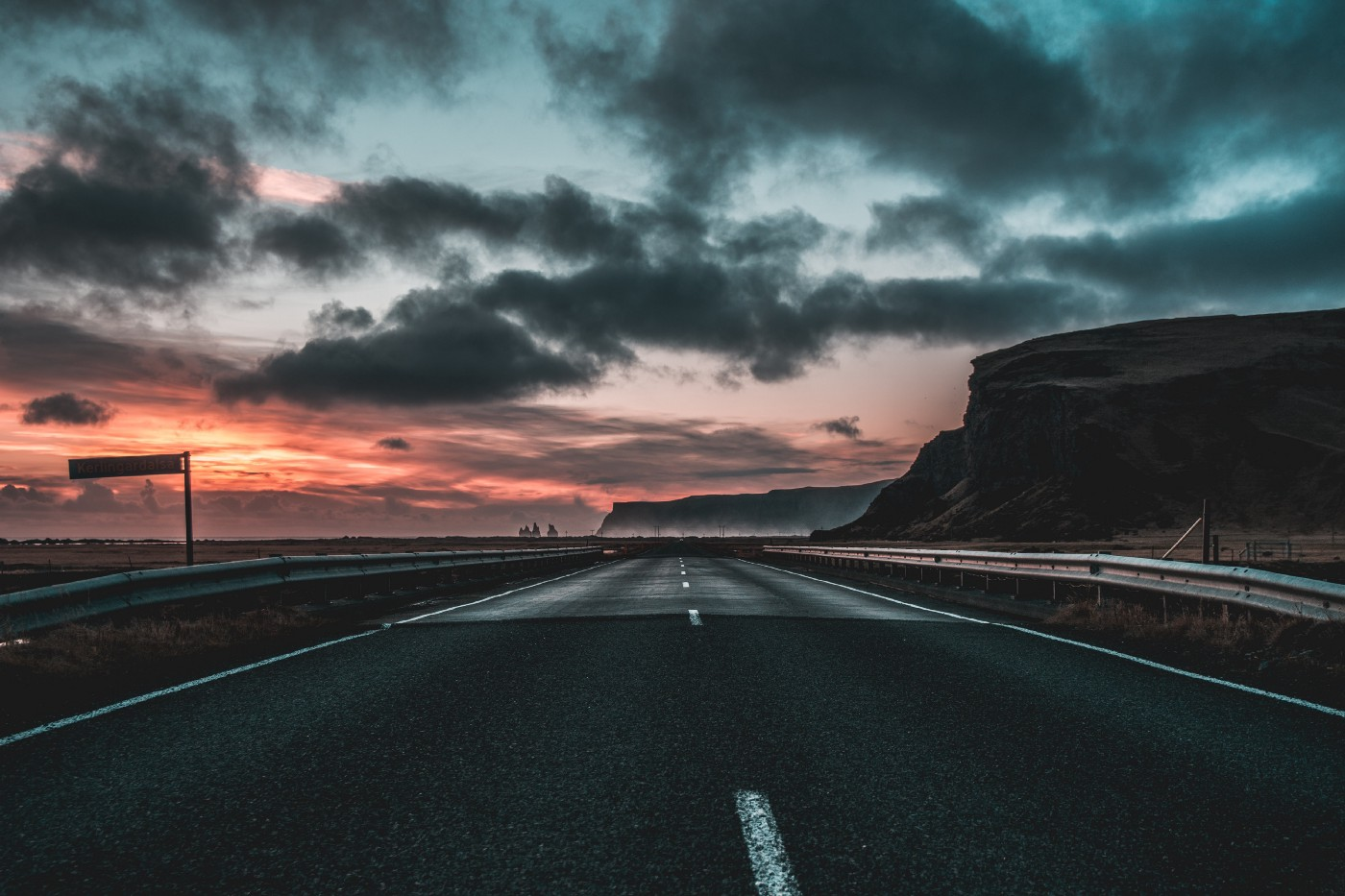 A long open highway with the sun rising and the sky turning crimson.