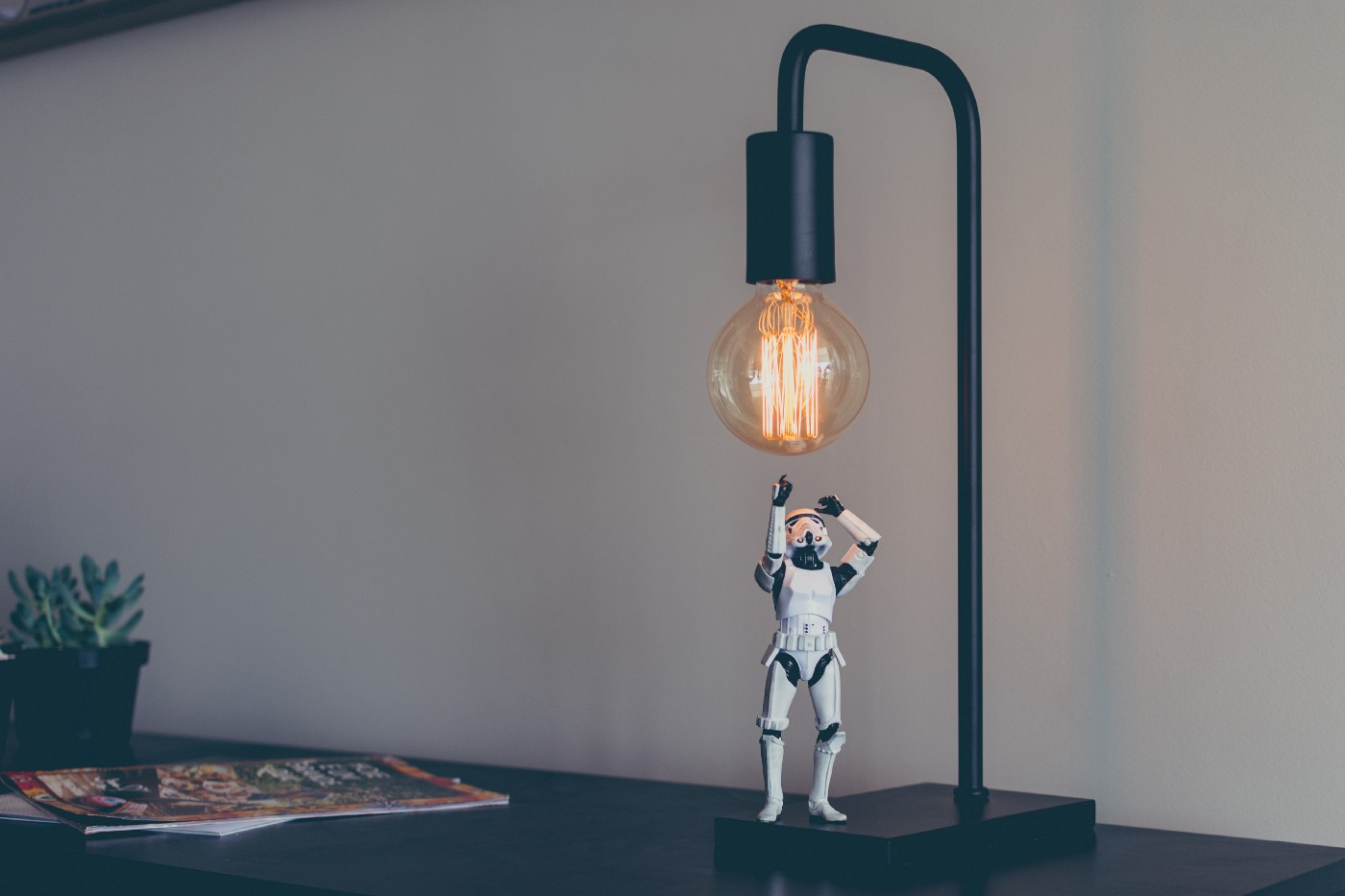 A small storm trooper toy looking up at a light bulb