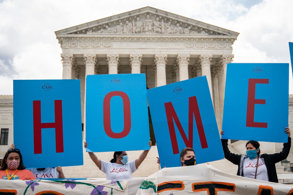 """DACA supporters hold up signs that read """"HOME"""" outside the Supreme Court on June 18th, 2020."""