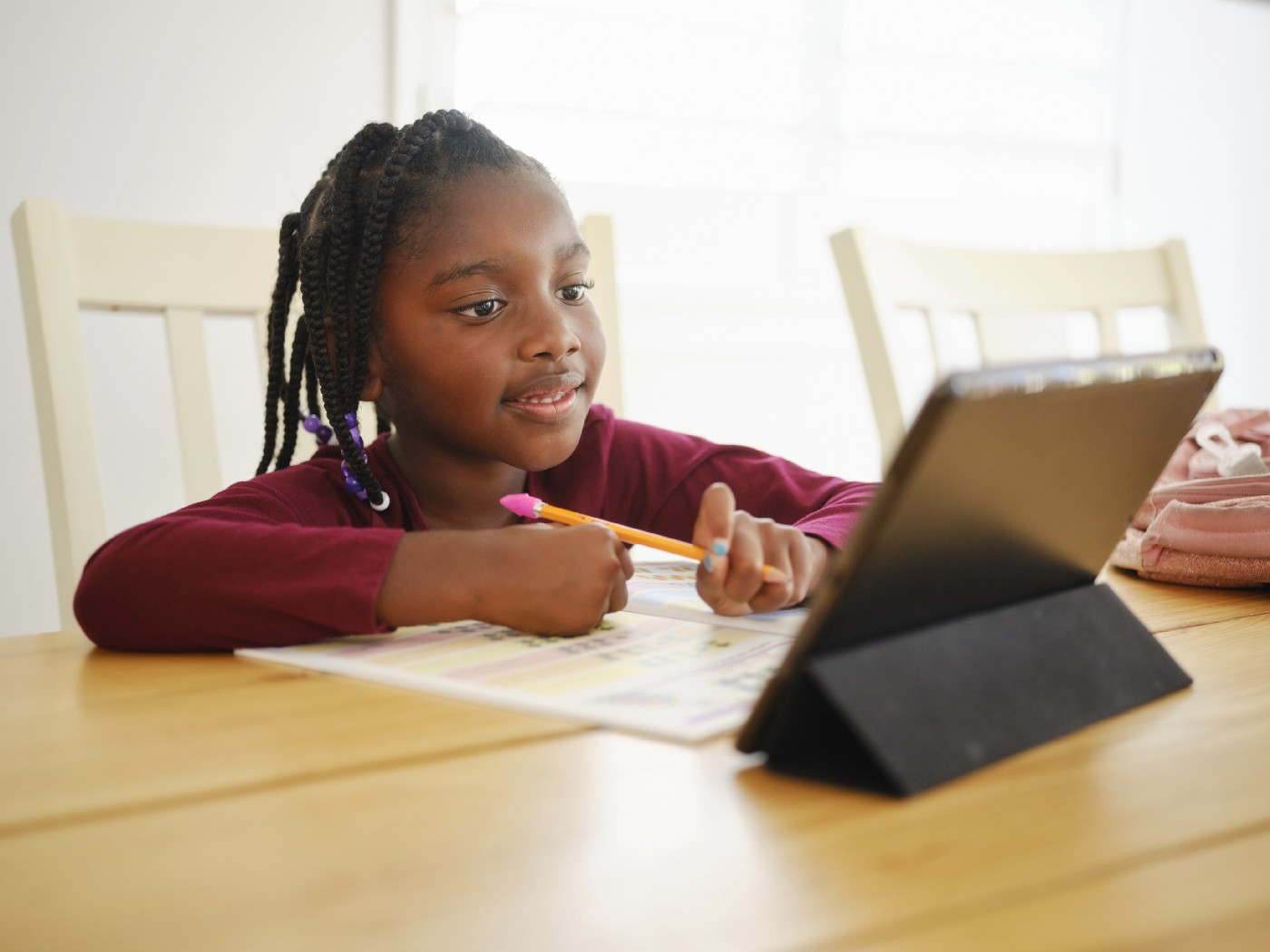 A young African American girl pays attention happily to her iPad tablet, learning remotely with a pencil in hand.