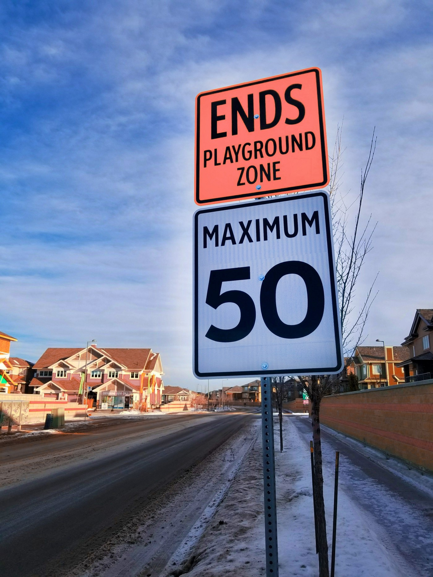 "A road sign reads ""ENDS PLAYGROUND ZONE"" . Below it, another sign reads MAXIMUM 50."