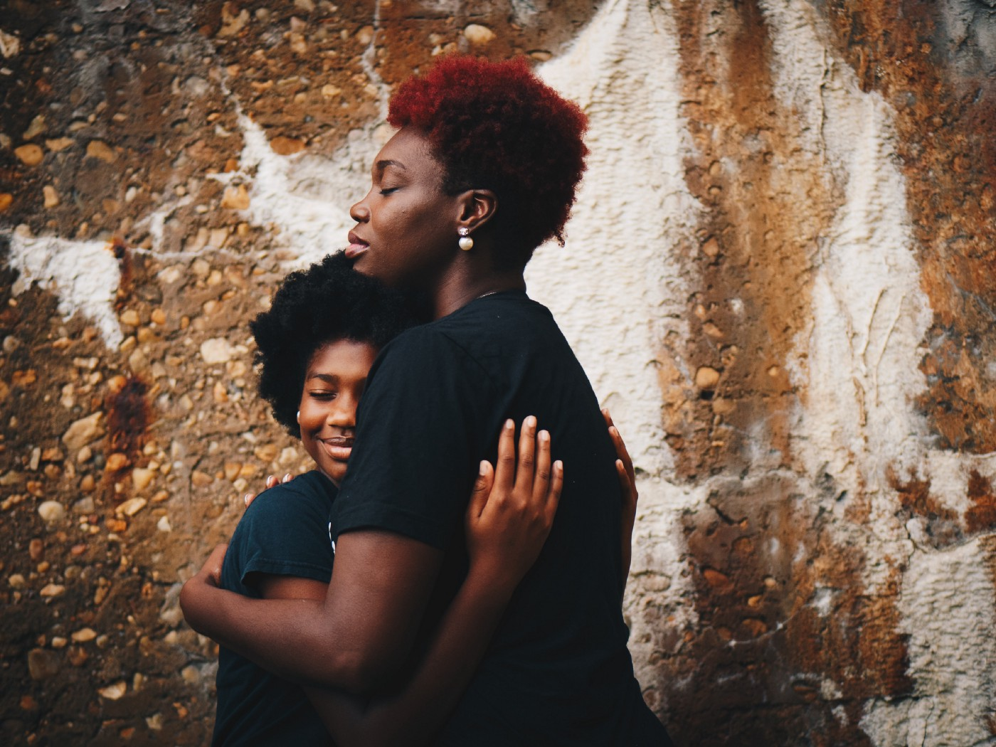 Black mother and daughter hug in front of a wall.