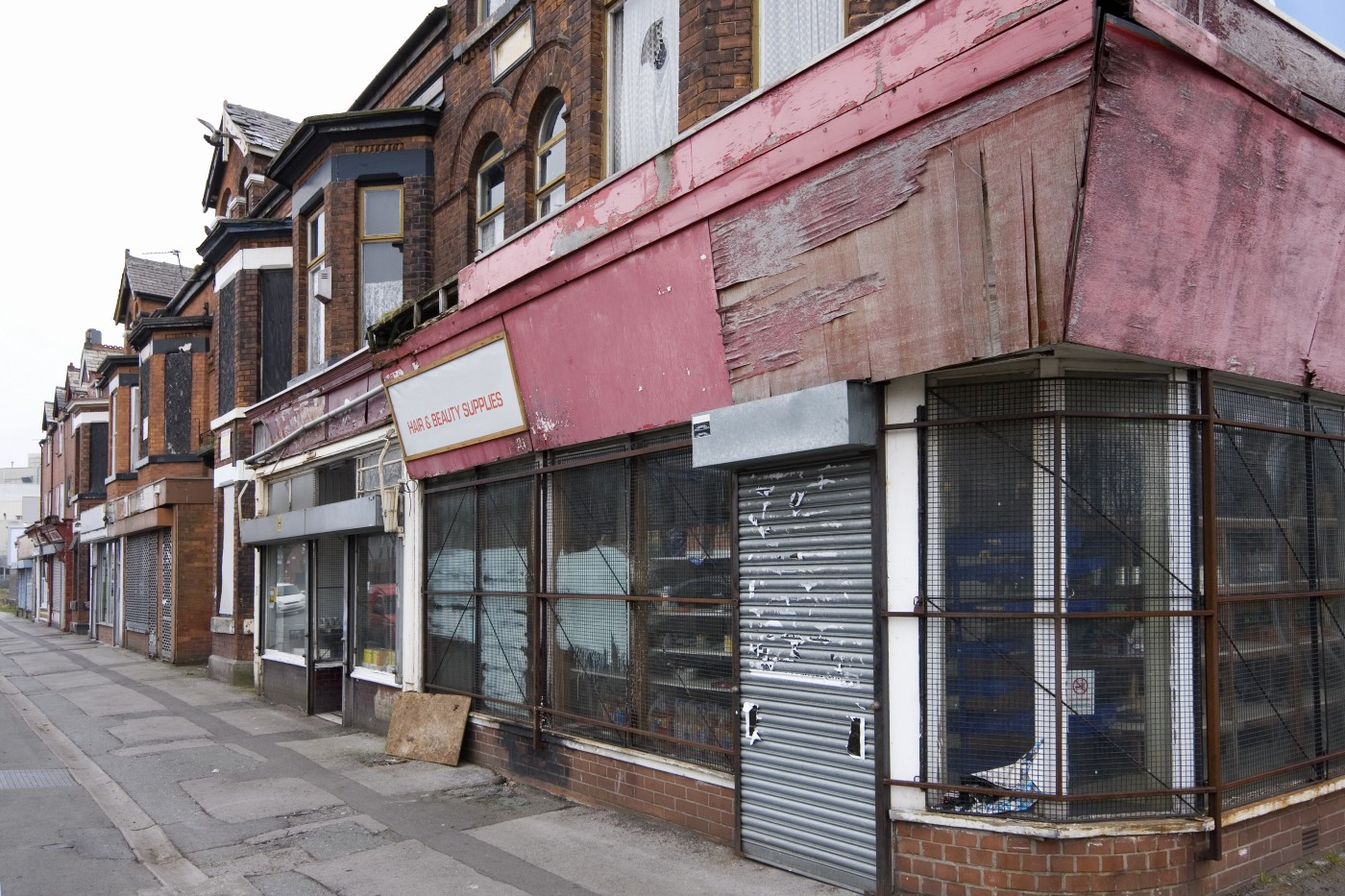 A row of shops that are boarded up on a street corner.