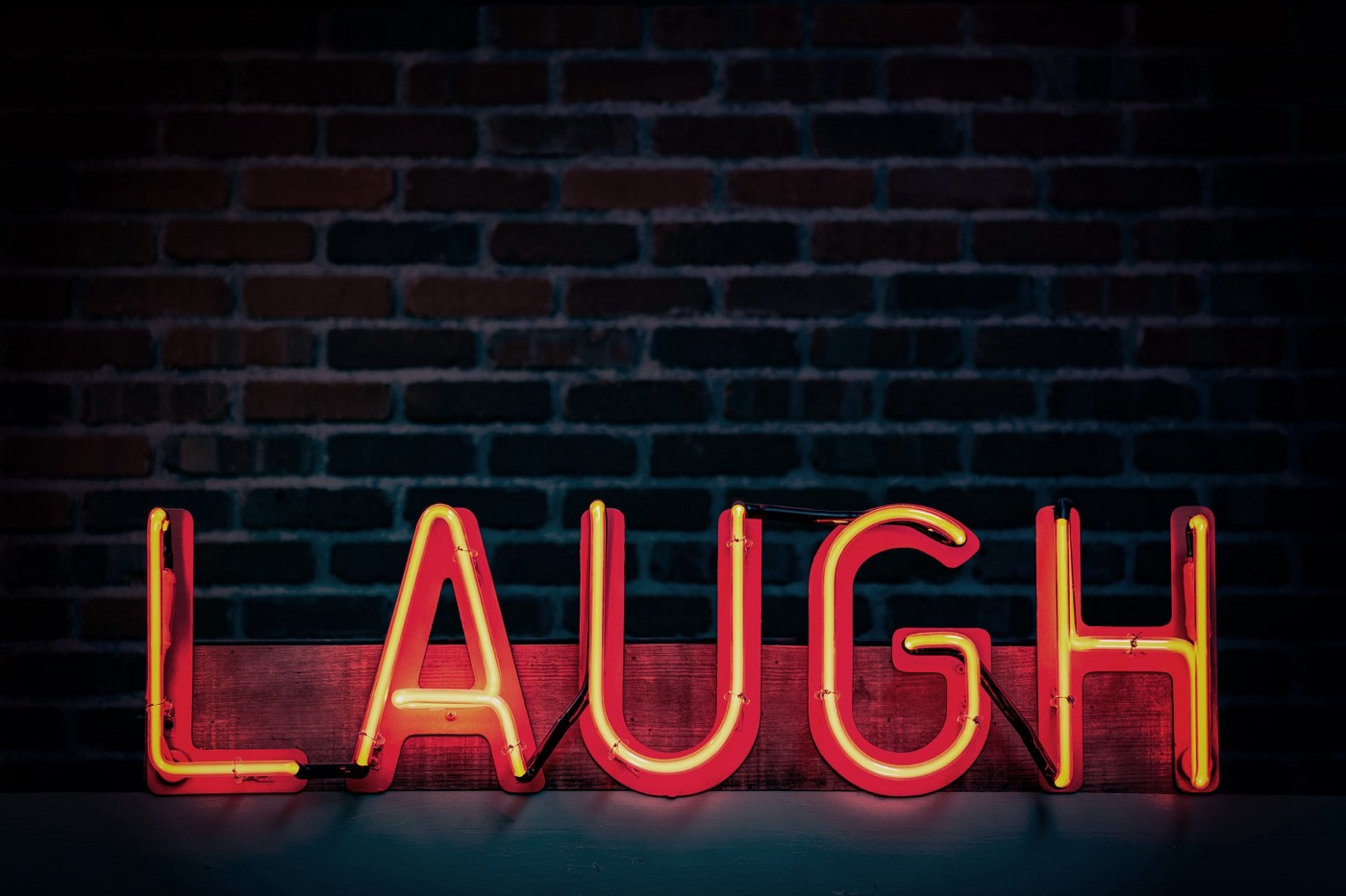 """A neon sign reading """"LAUGH"""""""