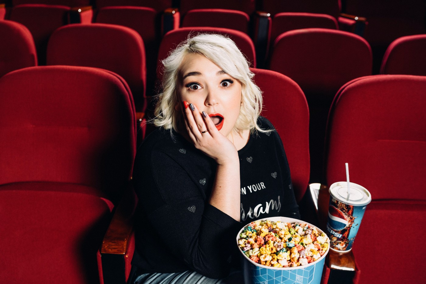 A blond woman in a red upholstered theater seat holds her hand to her mouth in astonishment while holding a bucket of popcorn and a soft drink.