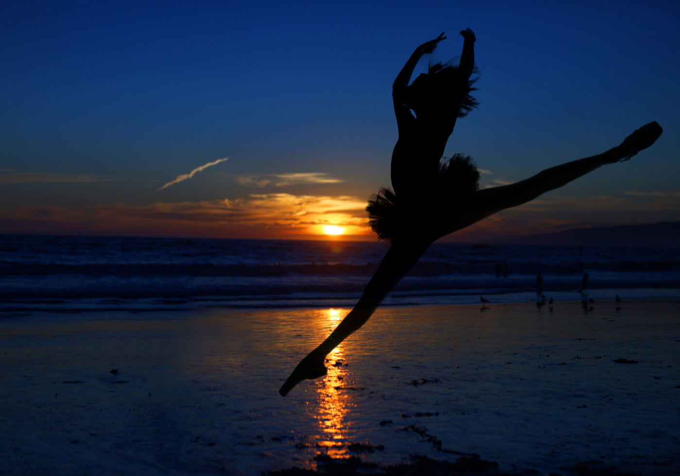 Silhouette of a ballerina pirouetting on a beach in front of the sun setting over the ocean.