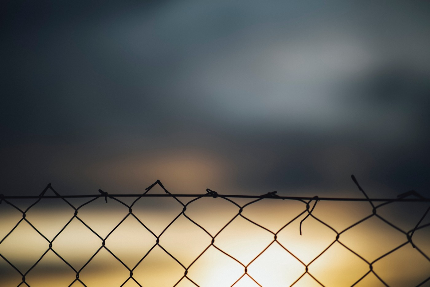Barbed wire fence with blurry brightness beyond