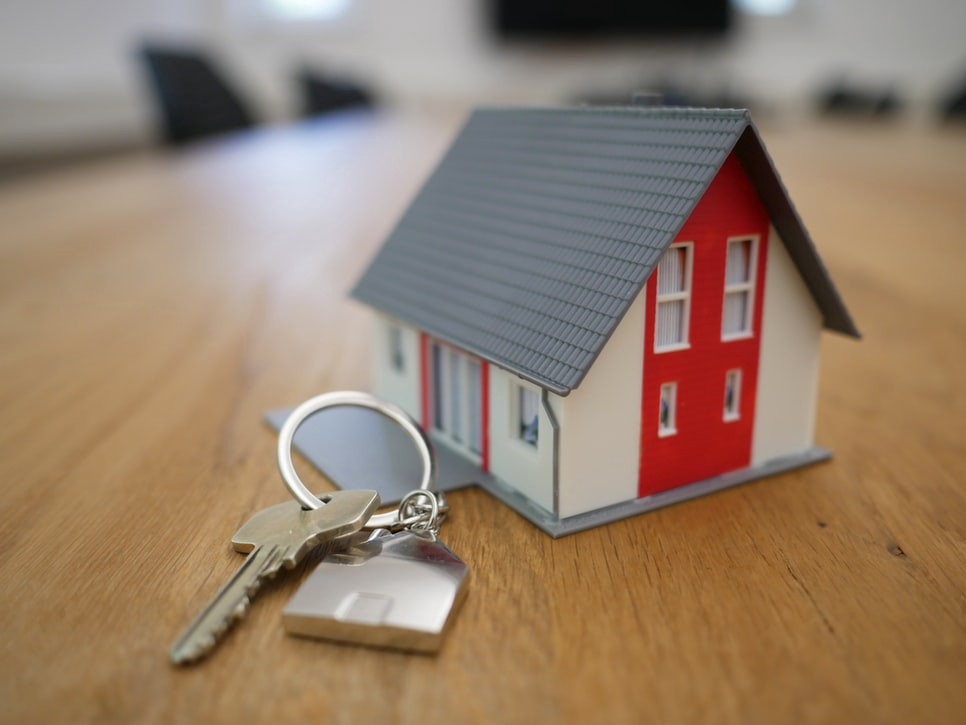 Gray, white, and red plastic model house on wooden desk next to house keys, real estate concept
