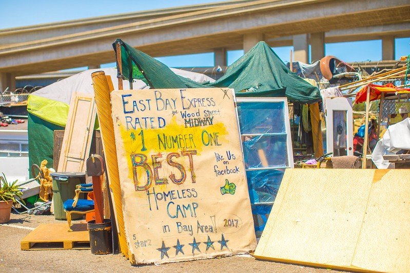 "Sign reads ""East Bay Express Rated #1 Number One Best Homeless Camp in Bay Area 2017. Large sign in front of a homeless camp in California."