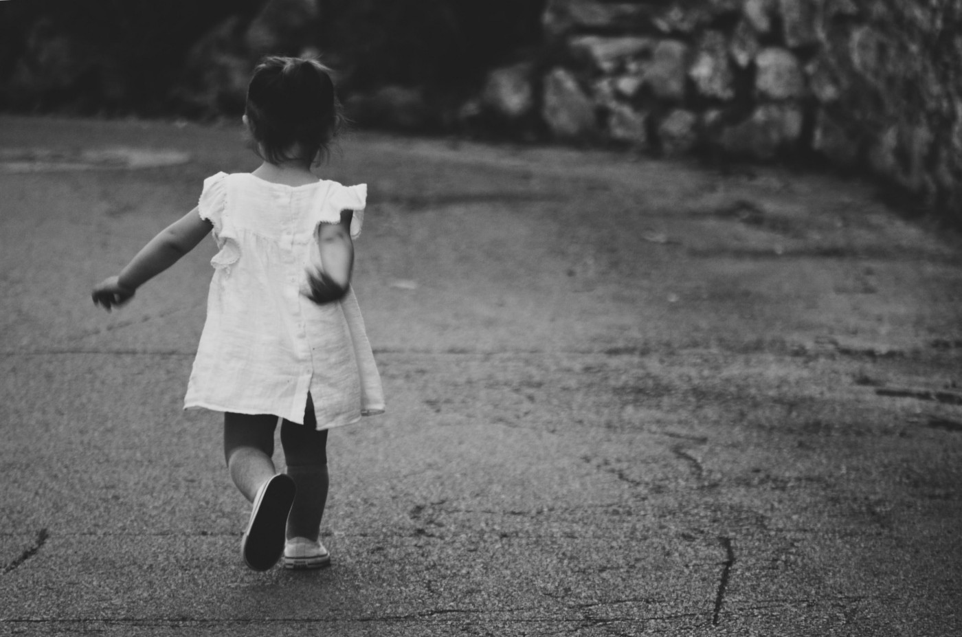 Little girl in a white dress and white shoes walking on a paved road with her back turned to the camera. Her hair is in a ponytail hair-do and some hedges are in the background.