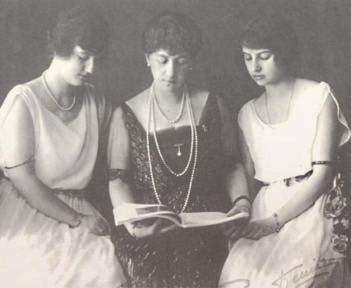 Maria in a black sparkly dress and pearls, sitting between her daughters in white dresses.