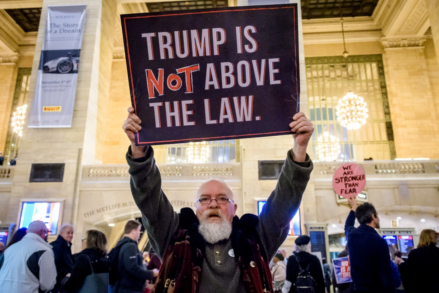 """A protestor holds a sign that says """"Trump is NOT above the law."""""""