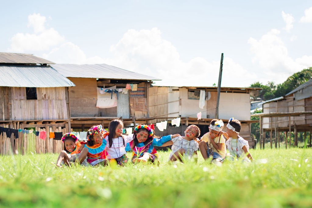 A group of Shawi children sit in the grass wearing their traditional clothing.