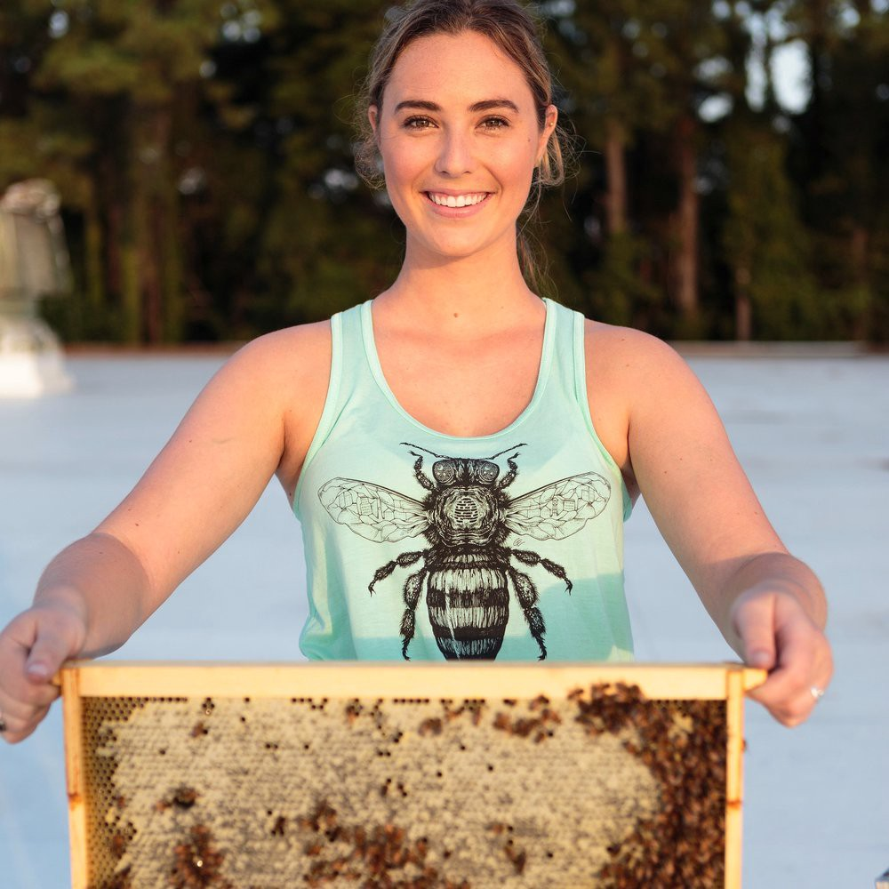 Leigh-Kathryn Bonner, founder of Bee Downtown holding a honeycomb frame from a bee hive.