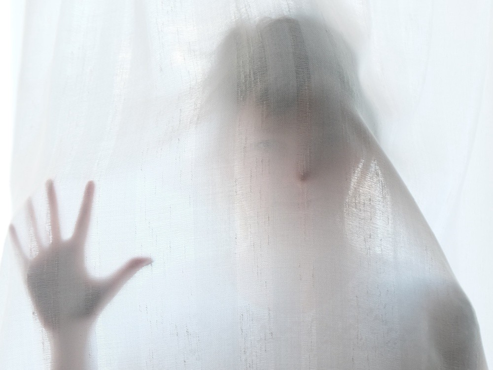 A woman behind an opaque sheet, looking like a ghost