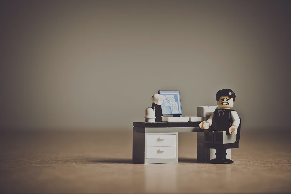 a lego toy office worker frustrated in front of a tiny computer
