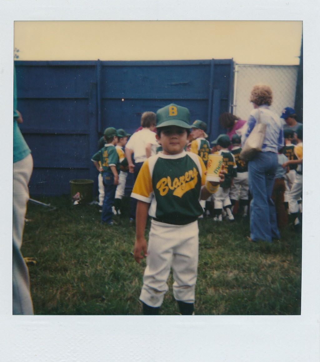 A young Hispanic boy is dressed in baseball gear, holding a soda can, circa 1980.