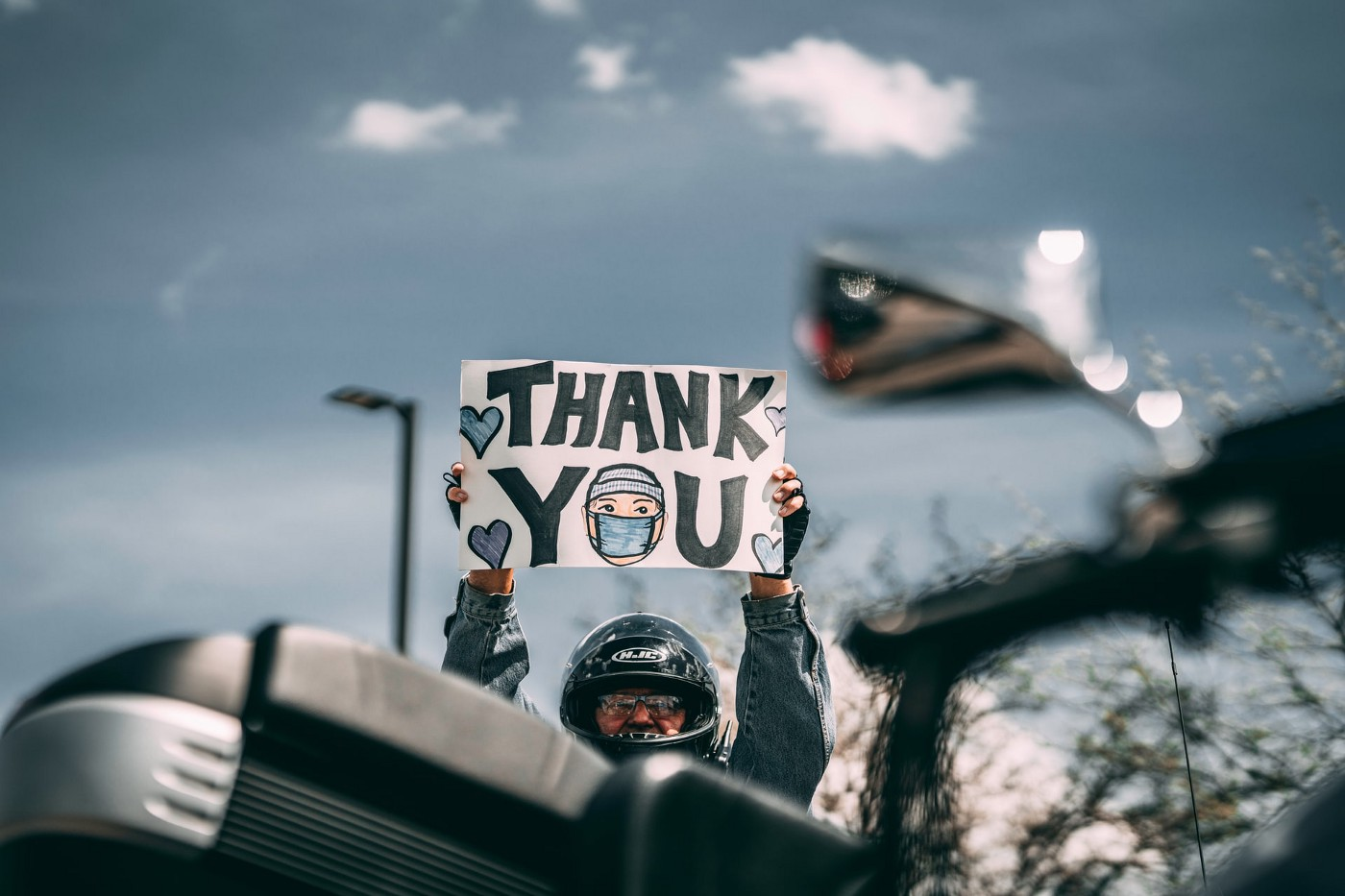 """Man standing next to motorcycle, wearing motorcycle helmet, and holding up a sign overhead that reads, """"Thank You."""""""