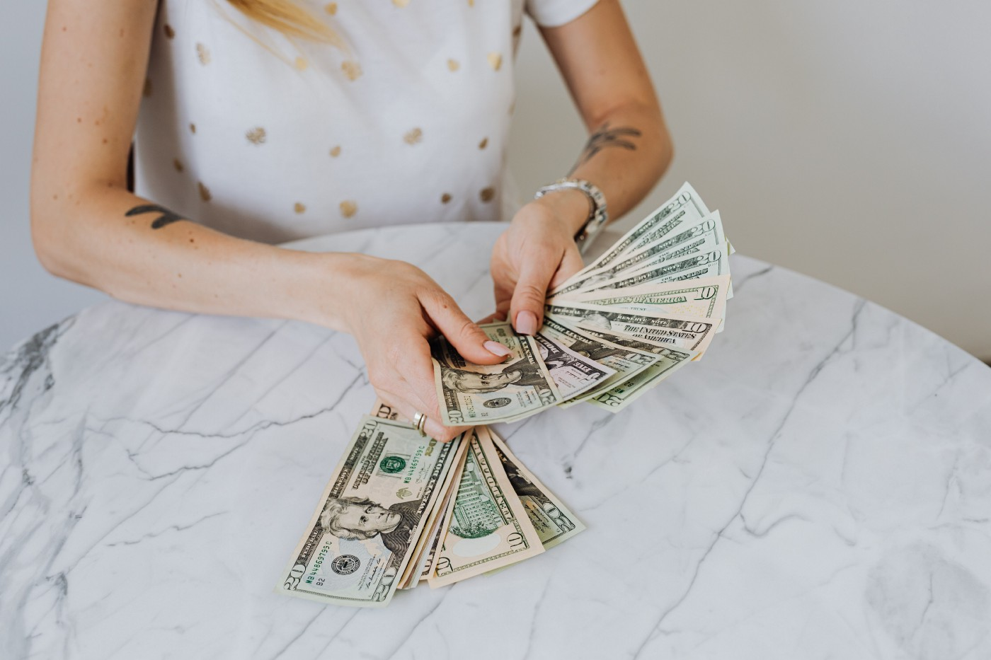 A feminine presenting person's torso is showing as they count twenty dollar bills on top of a round, white marble table. Their tattoos are visible on the inside of each arm as well as a watch on their left wrist.