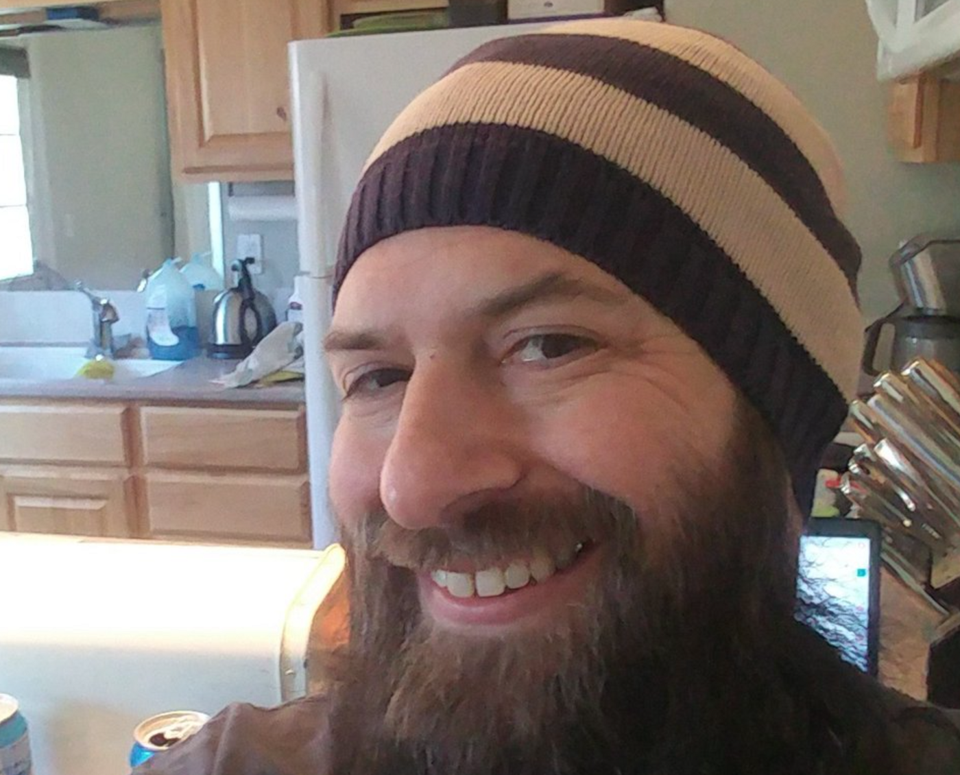 Photograph of the author, Hogan Torah, grinning, wearing beige and brown striped beanie hat. Full beard. Appears to be in kitchen.