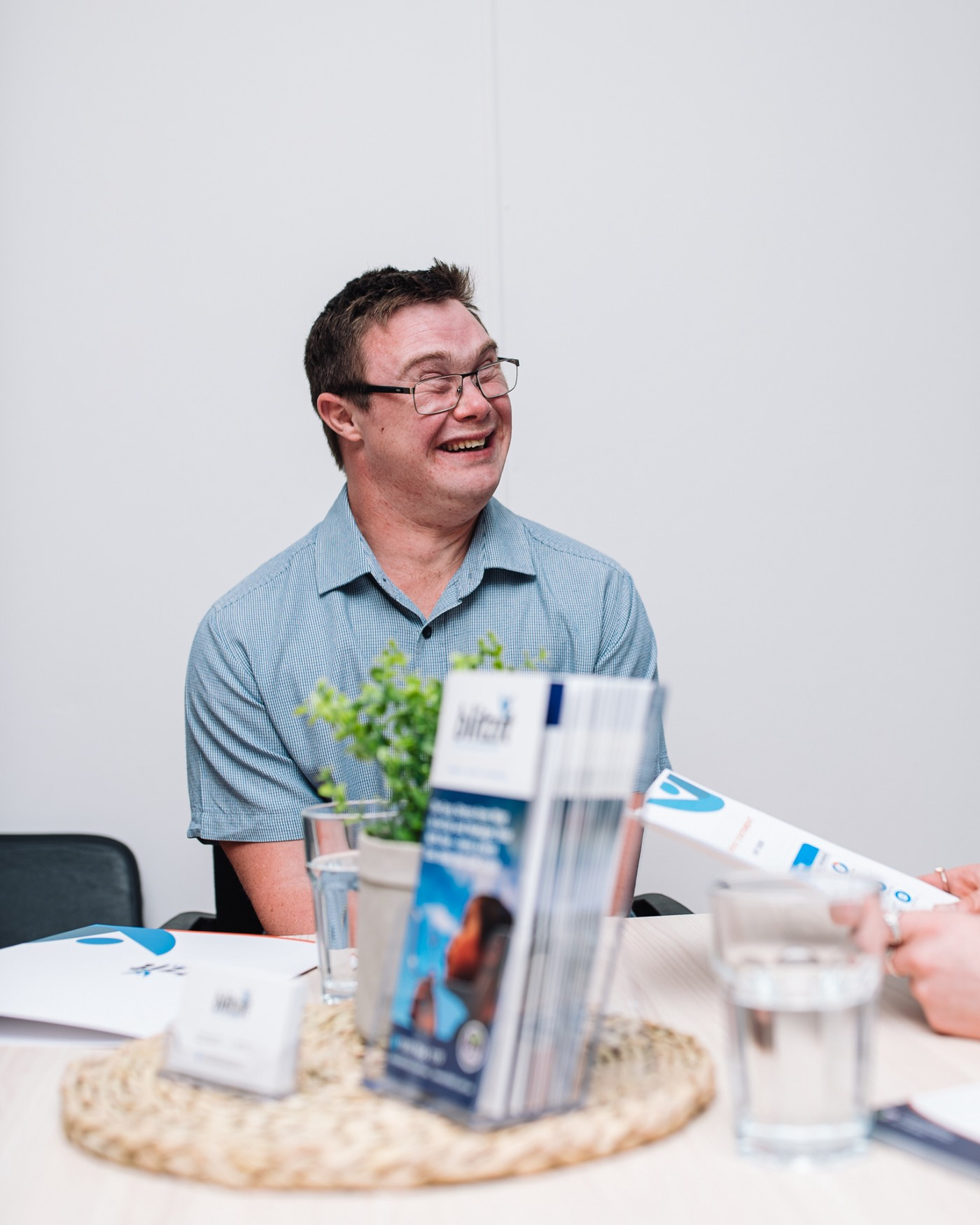 A male NDIS participants sits at a table,  with a plain white background. He is smiling, has short, brown hair, glasses  and a light blue shirt. The table has various items, including a green plant, Blitzit flyers and a glass of water.