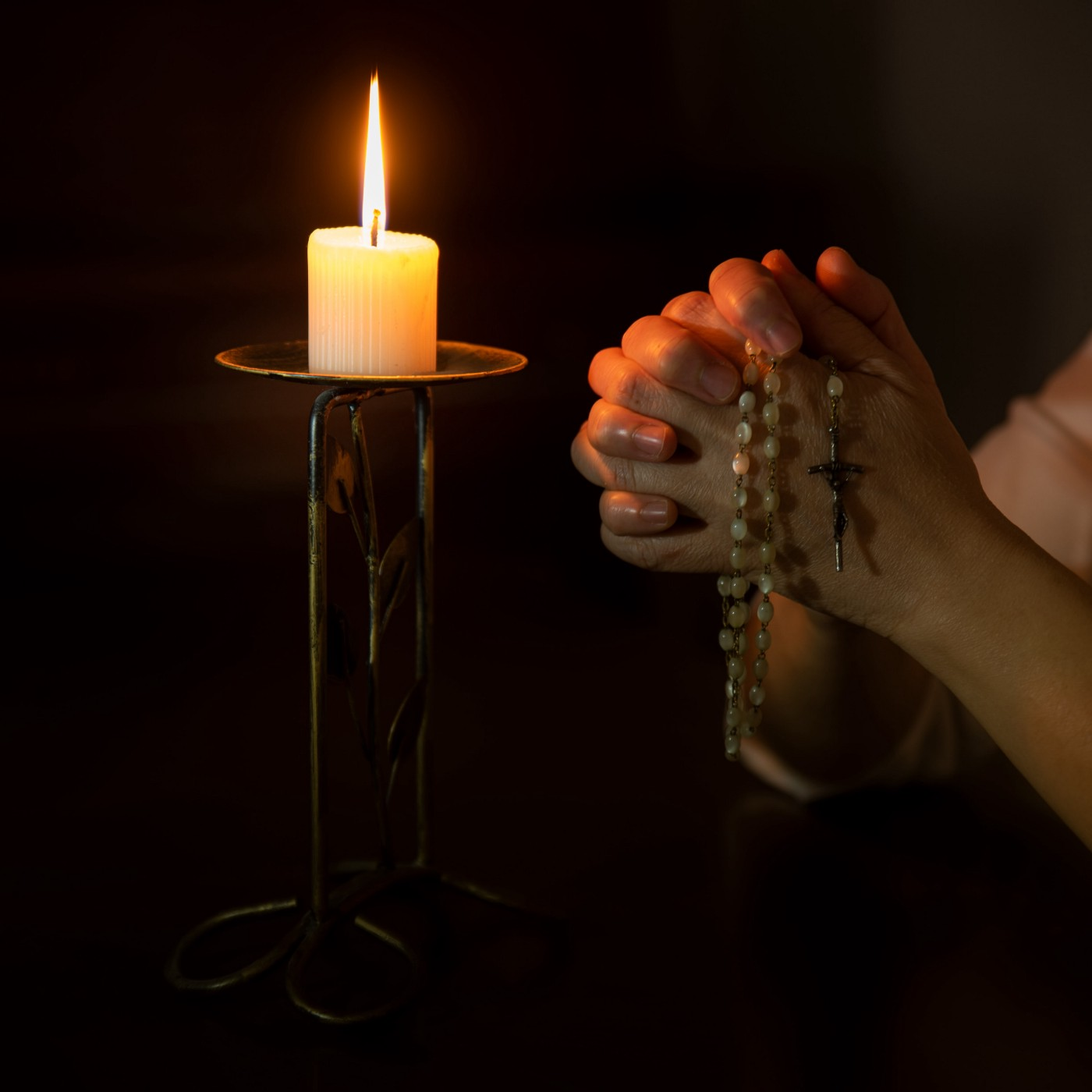 Person praying rosary on right and lit candle on left