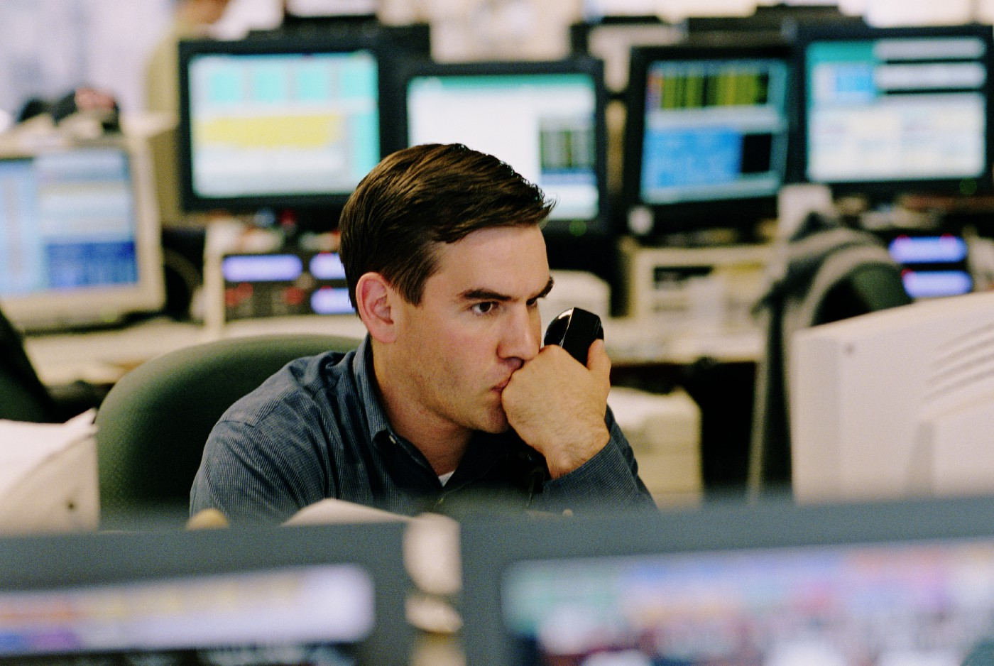 A broker contemplating and holding up a phone while watching his computer.