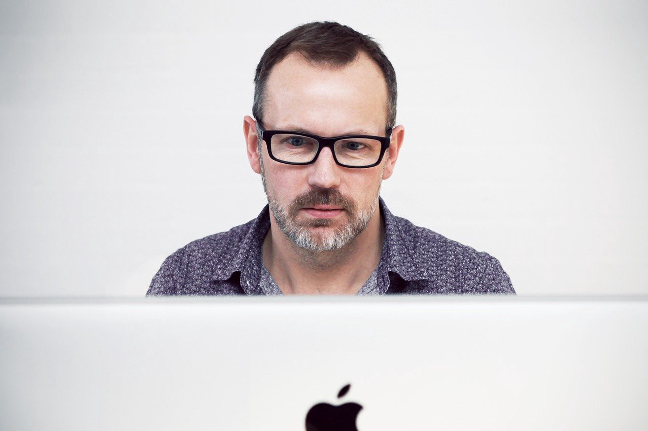 Man inquisitively reading Macbook.