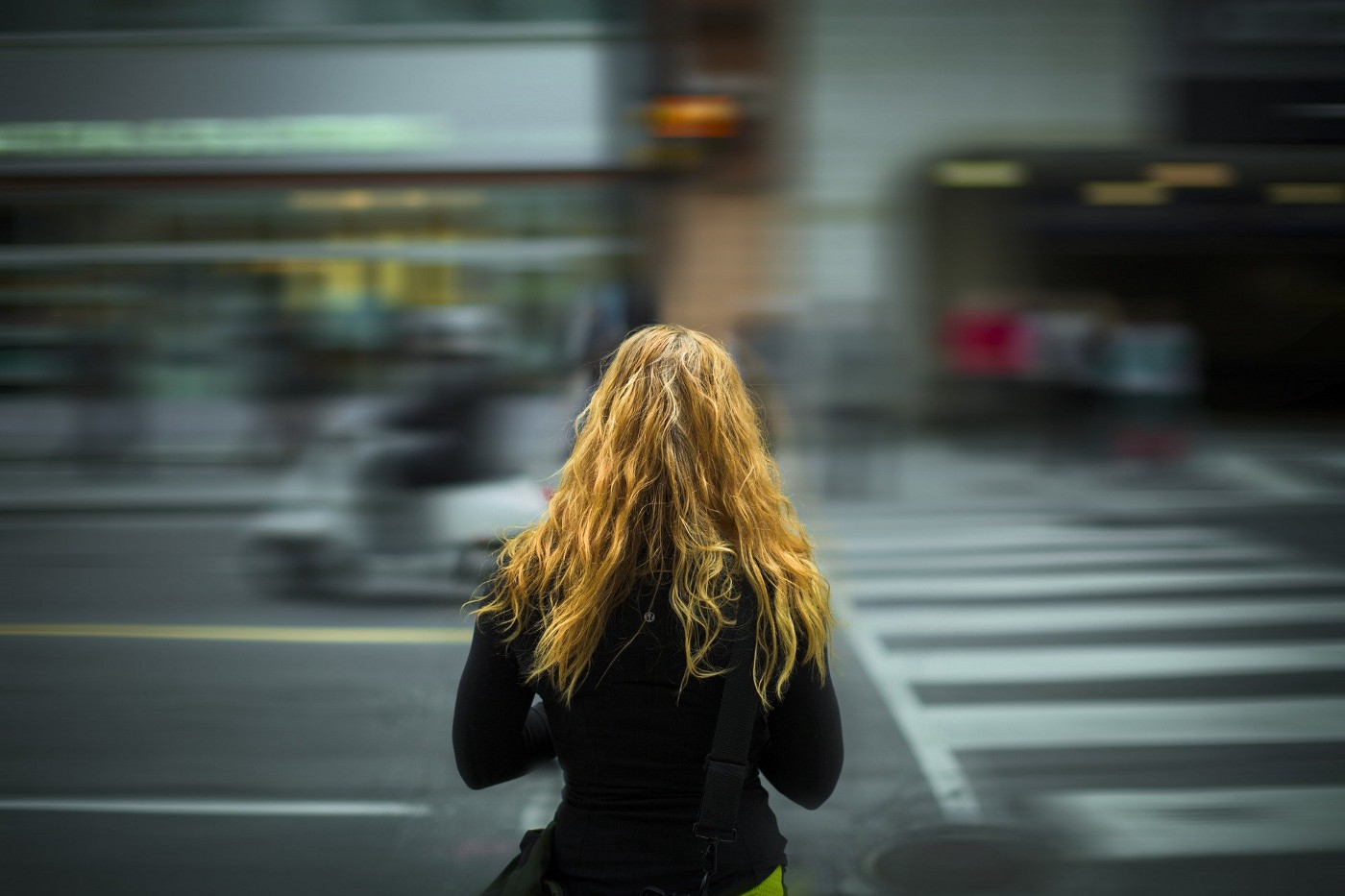 A woman with long, wavy brown hair and a dark top has her back to the camera, and is looking out onto a busy, blurred street.