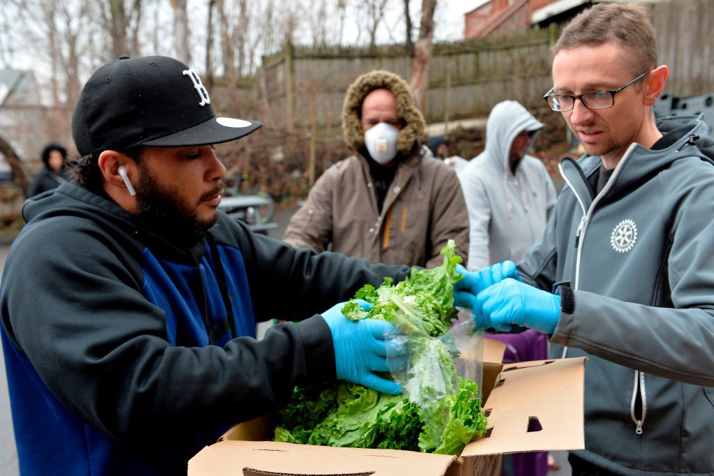 A photo of a group of volunteers gathering lettuce to give to people waiting in line for groceries.