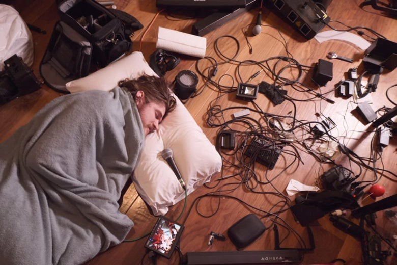 """A screenshot from """"Inside."""" Bo Burnham lays wrapped in a blanket with his head on a pillow. A plugged-in microphone rests gently next to his mouth, contrasting the chaotic jumble of cords on the floor next to him."""