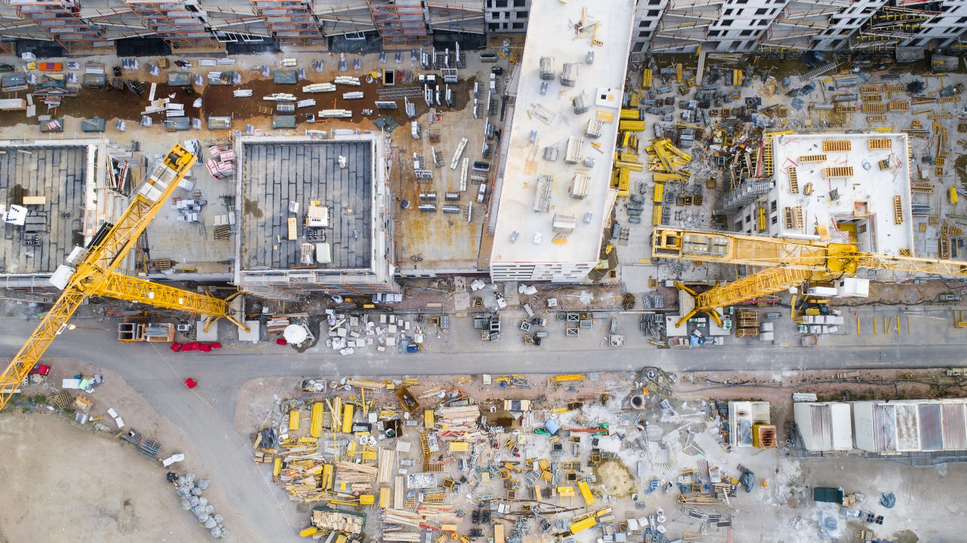 An aerial view of a construction worksite shows two yellow cranes among a sea of buildings and materials.