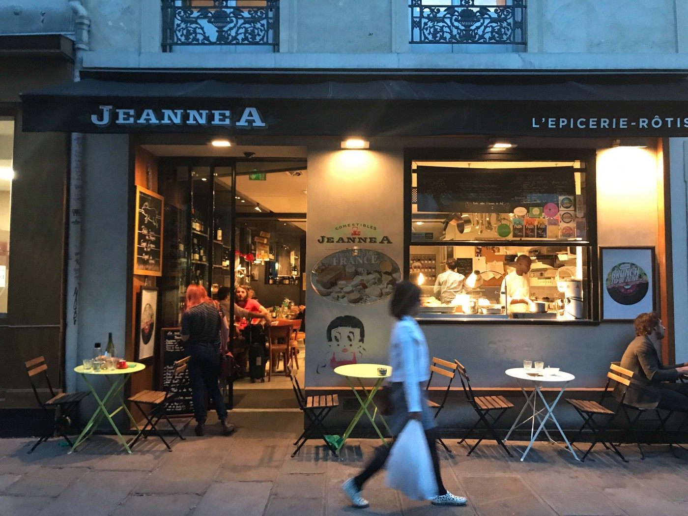 A woman carrying a white plastic bag walks by Paris restaurant JeanneA at night. The restaurant has sidewalk tables.