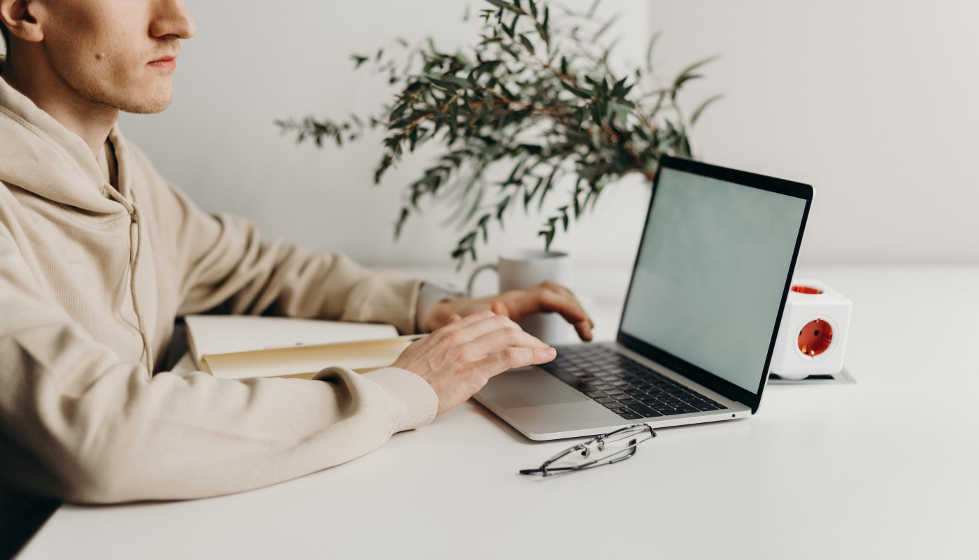 Man in off-white sweatshirt at a white desk types on a laptop