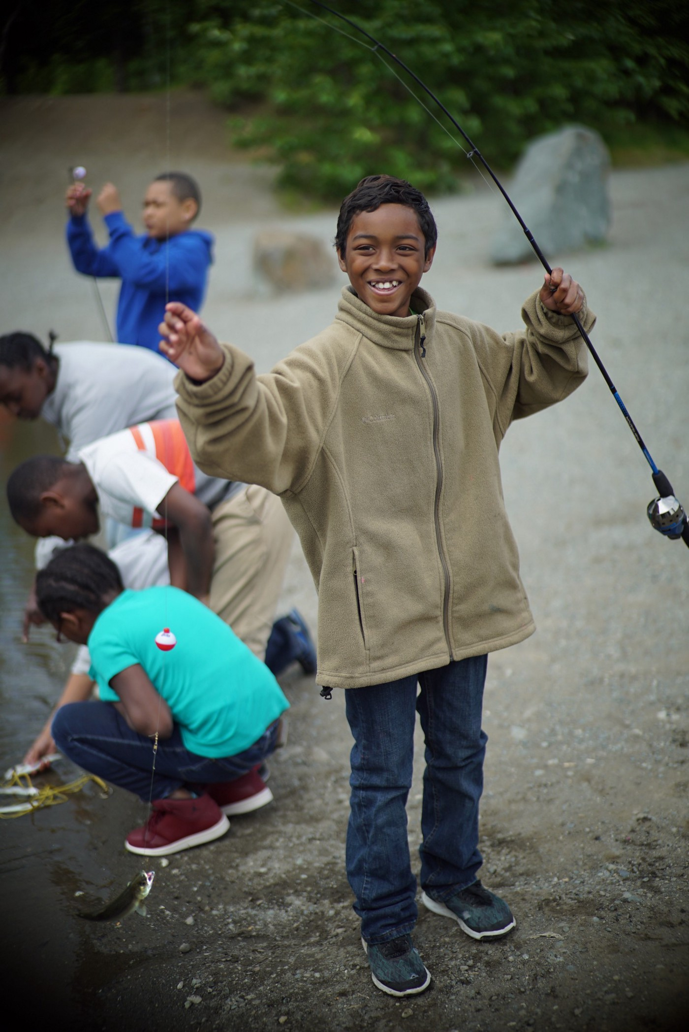 boy holding a small fish with a group of kids behind him