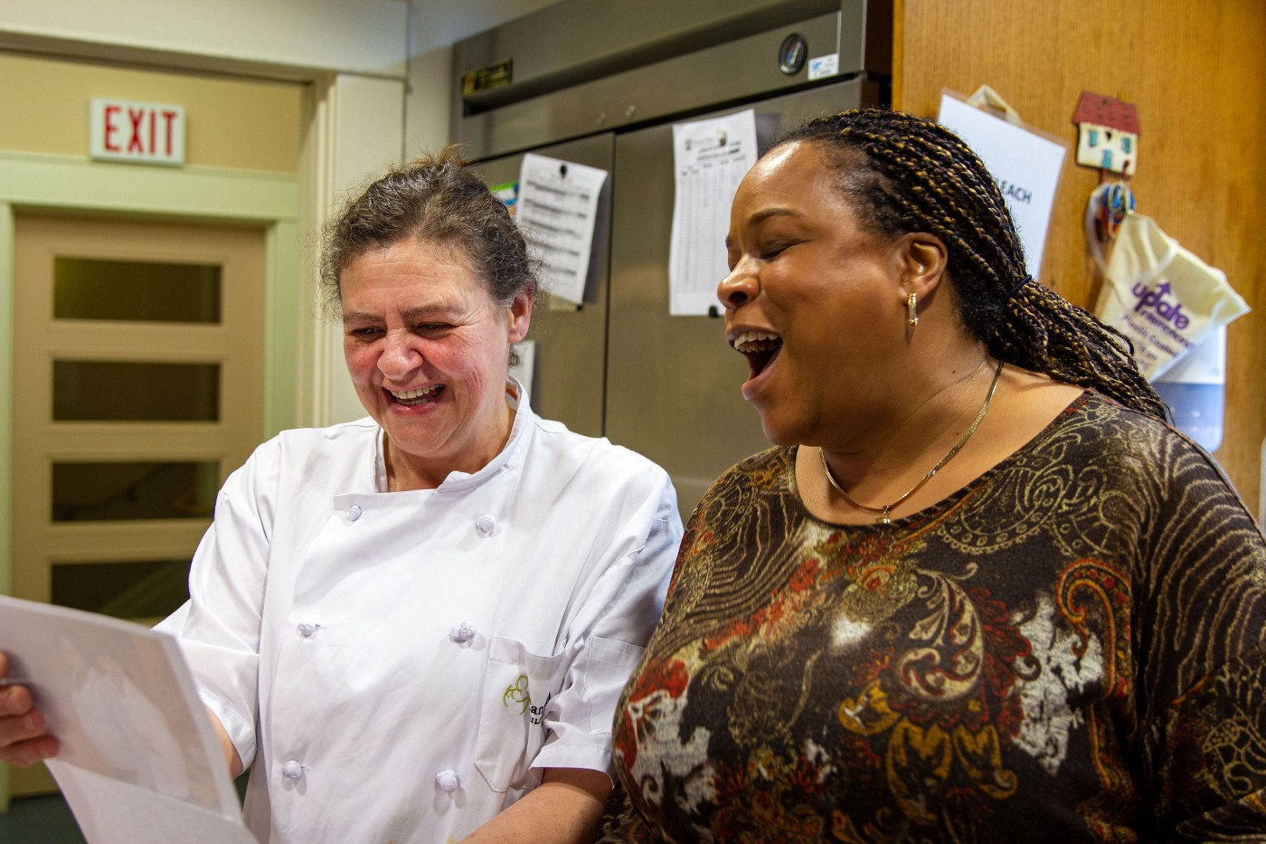 Two women laughing in the Canuck Place kitchen